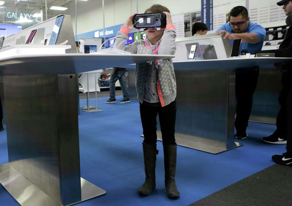 Aden Vervoort, 8, of Houston checks out a virtual reality set up for a phone while Black Friday shopping with her family at Best Buy on Friday, Nov. 24, 2017, in Houston.