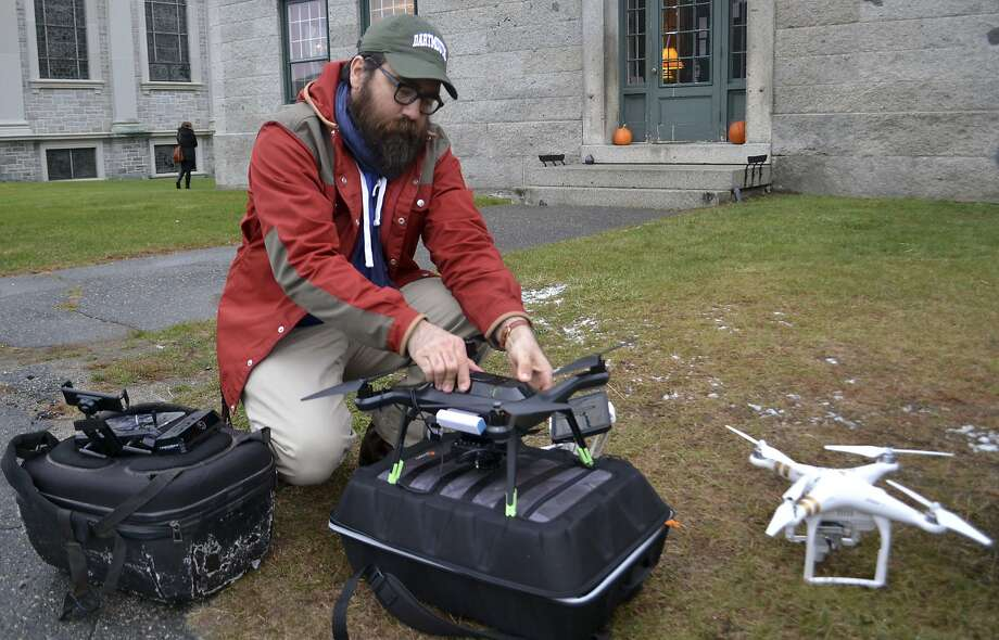 Dartmouth College archaeologist Chad Hill prepares a drone to be flown Nov. 14 over the site of a Shaker village in Enfield, N.H. Hill equipped the drone with a thermal imaging camera. Photo: Michael Casey, Associated Press