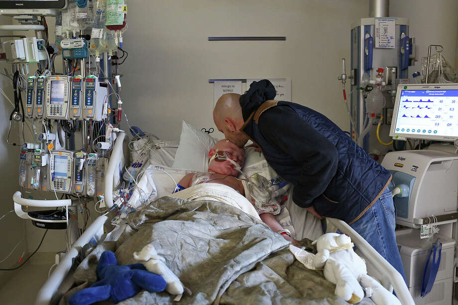 Brian kisses Rowan as Brian's stem cells flow into Rowan's body from bag hanging on the IV pole, left, in the pediatric intensive care unit at Seattle Children's Hospital on Oct. 18, 2016. The cells were Rowan's second transplant in three months. Despite the second transplant, Rowan died Dec. 15, 2016, from multiple organ failure and sepsis.