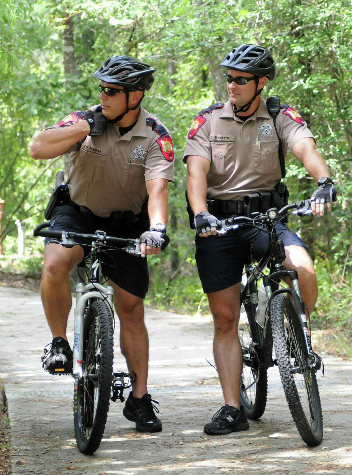 Montgomery County Sheriff's Department Bike Patrol deputies David Haines and Chris Roberts call in a suspicious vehicle license as they ride a patrol on one of the bike paths in The Woodlands. The bike patrols have started more patrols into residential neighborhoods following recent assaults on the bike paths. Photo by David Hopper.