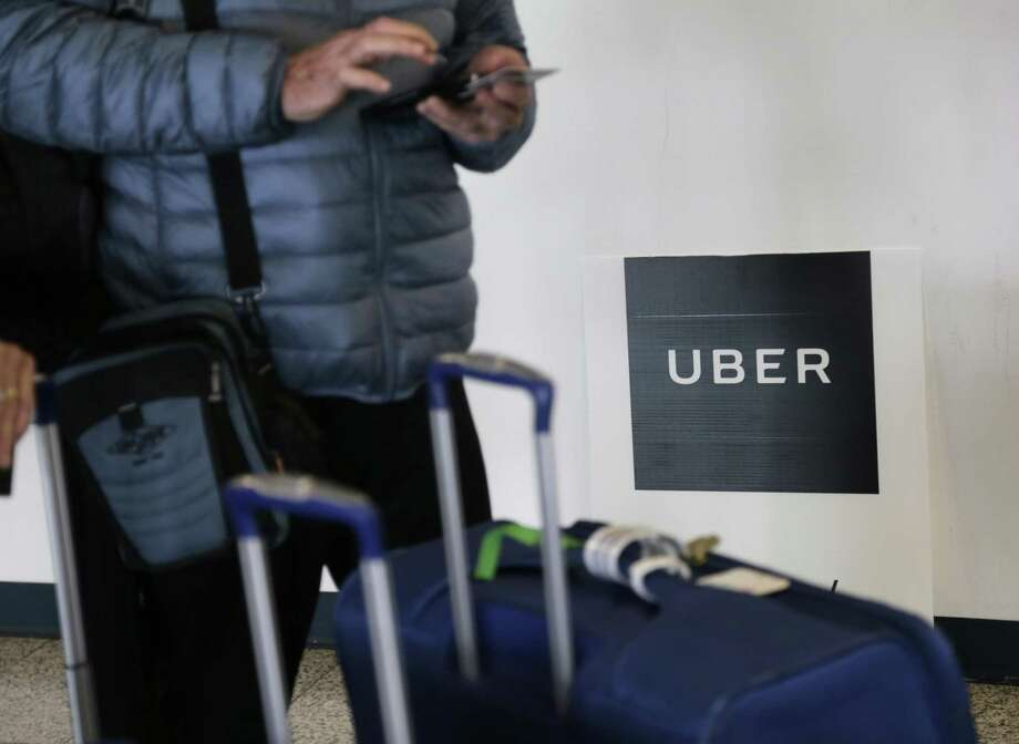 A traveler tries to book a ride with Uber at LaGuardia Airport in New York. Through a string of almost weekly scandals, Uber has managed to continue growing and hold onto the title of the worlds largest ride-hailing service. Photo: Seth Wenig /Associated Press / Copyright 2017 The Associated Press. All rights reserved.