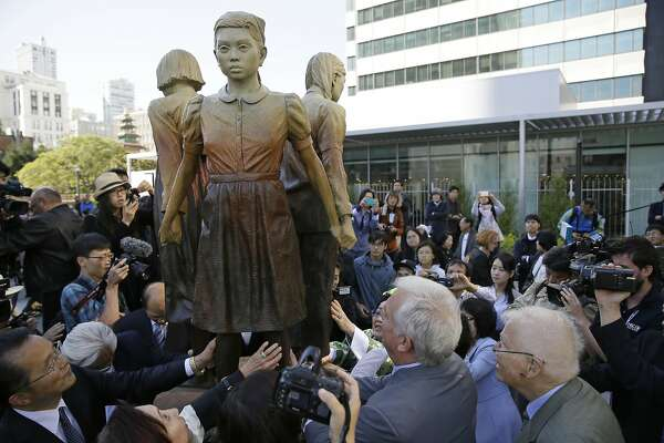 "FILE - In this Friday, Sept. 22, 2017, file photo, people move in to take a closer look at the ""Comfort Women"" monument after it was unveiled in San Francisco. Japan has expressed strong regret over San Francisco's decision to give formal city property status to a statue commemorating women who worked in military-backed brothels for Japanese troops during World War II, with Osaka declaring it will terminate its 60-year sister-city ties. (AP Photo/Eric Risberg, File)"