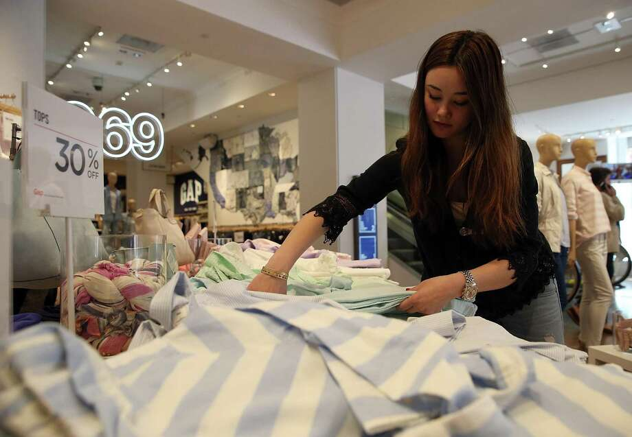 A Gap employee folds clothes at a Gap store in San Francisco. Researchers say women who work in restaurants and clothing stores tend to encounter more predatory behavior than those in glitzier professions. Photo: Justin Sullivan /Getty Images / 2014 Getty Images