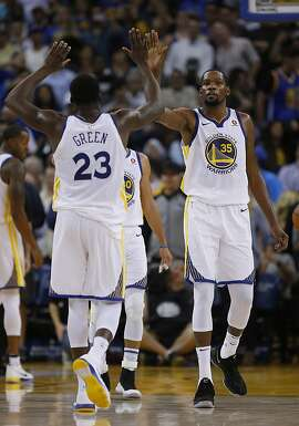 Golden State Warriors forward Kevin Durant (35) high-fives Draymond Green (23) during the fourth quarter of an NBA game between the Golden State Warriors and Toronto Raptors at Oracle Arena on Wednesday, Oct. 25, 2017, in Oakland, Calif. The Warriors won 117-112.