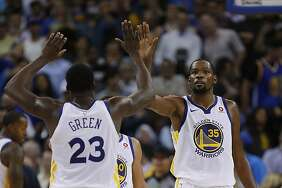 Golden State Warriors forward Kevin Durant (35) high-fives Draymond Green (23) during the fourth quarter of an NBA game between the Golden State Warriors and Toronto Raptors at Oracle Arena on Wednesday, Oct. 25, 2017, in Oakland. The Warriors won 117-112.