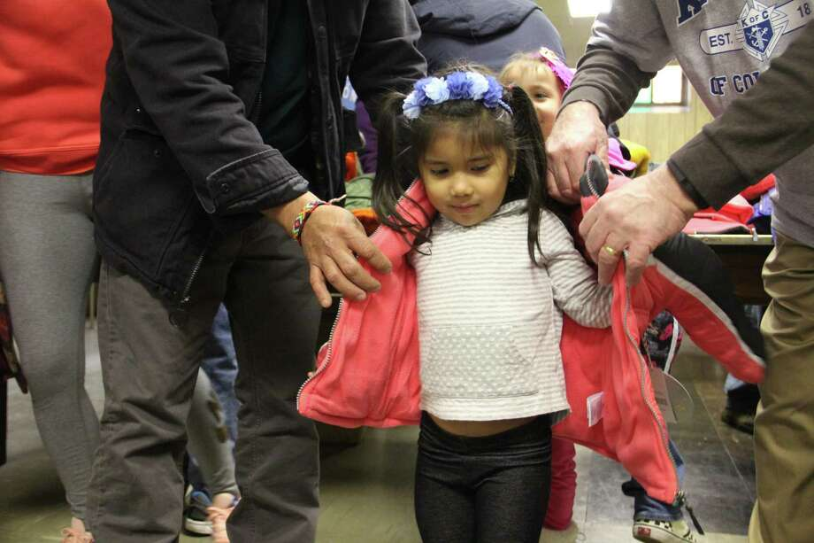 Scarlett Balvuca, 2, receives a free coat from the Knights of Columbus Coats for Kids drive on Friday, Nov. 24, at St. John the Baptist Church in New Haven. Organizers said 300 coats were available for children. Photo: Esteban L. Hernandez / Hearst Connecticut Media