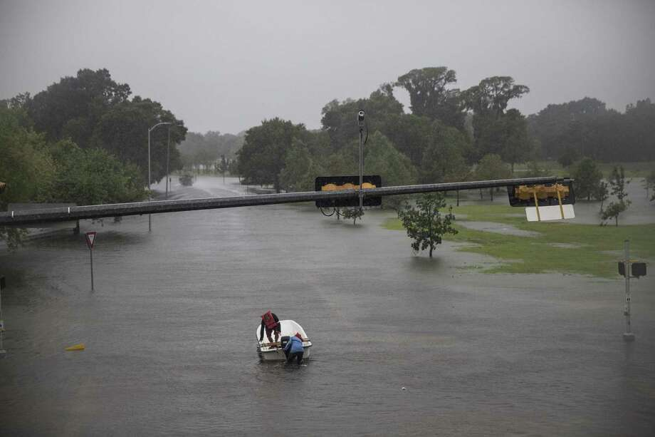 People attempt to get their boat moving through flood waters after Hurricane Harvey in Houston Aug. 28. Federal disaster aid to Texas has been lacking. Photo: TAMIR KALIFA /NYT / NYTNS