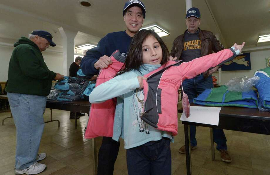 Alexandra Garcia, 7, tries on a new coat with the help of Chris Lau during the Knights of Columbus annual Coats for Kids program Friday, Nov. 24, at St. Joseph Church in South Norwalk. As part of the Neighbors Helping Neighbors initiative, the Coats for Kids program allows councils across North America to purchase new winter coats for children at a discount and to distribute them to children in need in their local communities. Since the programs launching in 2009, more than 370,000 coats have been distributed in 49 states and all 10 Canadian provinces. Photo: Erik Trautmann / Hearst Connecticut Media / Norwalk Hour