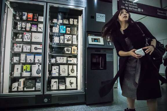 Soyeon Moon purchases earbuds and rushes to her flight from a Best Buy vending machine manufactured by Swyft, at SFO arrivals on Friday, Nov. 17, 2017 in San Francisco, CA