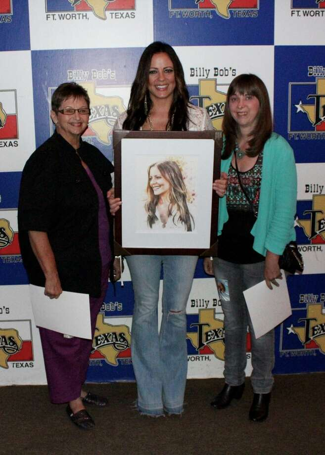 Graphic artist Jennifer Johnson (far right) and her mother Carolyn (far left) pose with musical artist Sara Evans in a provided image. Johnson's art has placed her in close proximity with many musical artists. Provided by Jennifer Johnson / www.jenniferjohnsonart.com Photo: Provided