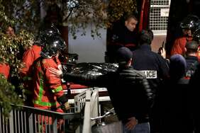 "Police officials and rescue personnel transport the body of a tiger which had escaped from a circus into a vehicle in Paris on November 24, 2017, after the tiger was shot following an escape in the French capital. A tiger which escaped from a circus in Paris has been ""neutralized"" by circus personnel and is now dead, police said. Firefighters had been called around 1700 GMT by people who saw the animal in the 15th Arrondissement of the French capital.s)"