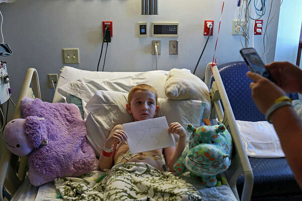 Rowan Windham holds up a sign indicating the number of surgeries he's had before the day's surgery on June 2, 2015. His mom had him hold a sign with the surgery number for every surgery in the operating room at Methodist Children's Hospital in San Antonio.