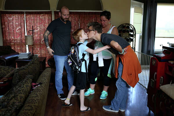 Brian and Carrie stand by as Rowan and his brother, Ian, 17, kiss  goodbye before Carrie and Rowan left New Braunfels on July 1, 2016, to  drive to Seattle for Rowan's transplant.