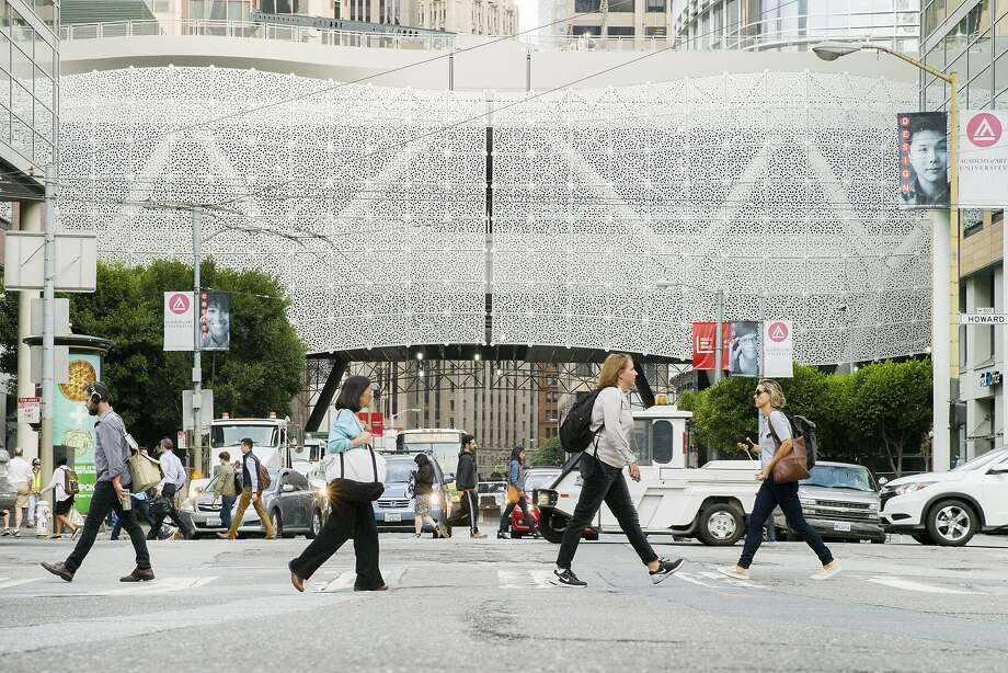 Pedestrians pass by the nearly completed Transbay Transit Center in September. Wiring of the terminal is not expected to be finished until March, pushing back the opening. Photo: Santiago Mejia, The Chronicle