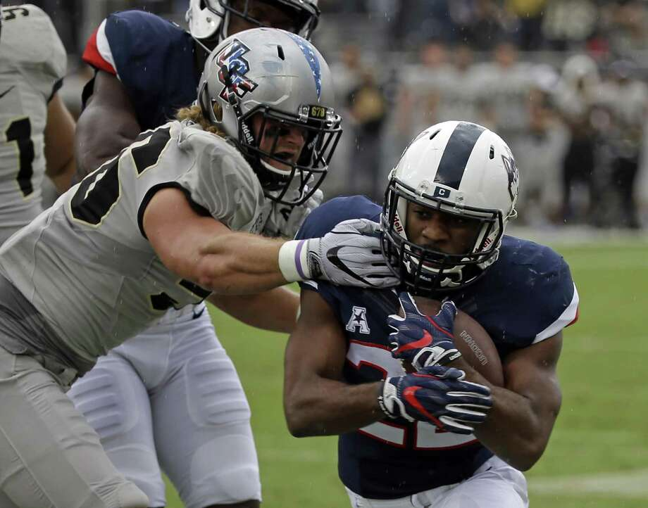 Connecticut running back Arkeel Newsome, right, is tackled by Central Florida linebacker Pat Jasinski during the first half of an NCAA college football game, Saturday, Nov. 11, 2017, in Orlando, Fla. (AP Photo/John Raoux) Photo: John Raoux / Associated Press / Copyright 2017 The Associated Press. All rights reserved.