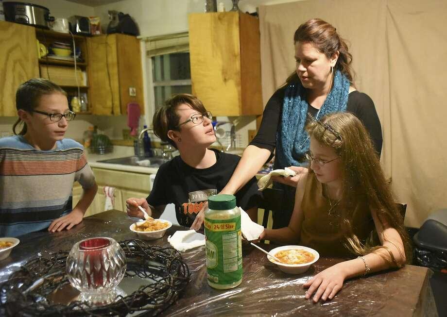 Dakota Flores serves dinner to her children, Tyler Reinn, left, Serenity Grace and Harmonie Lovve. Harmonie Lovve and Tyler Reinn rely on the CHIP program for health insurance. Photo: Billy Calzada