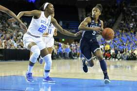 Connecticut guard Crystal Dangerfield (5) drives as UCLA guard Kennedy Burke (22) defends in the first quarter of an NCAA women's basketball game in Los Angeles Tuesday, Nov. 21, 2017. (AP Photo/Reed Saxon)