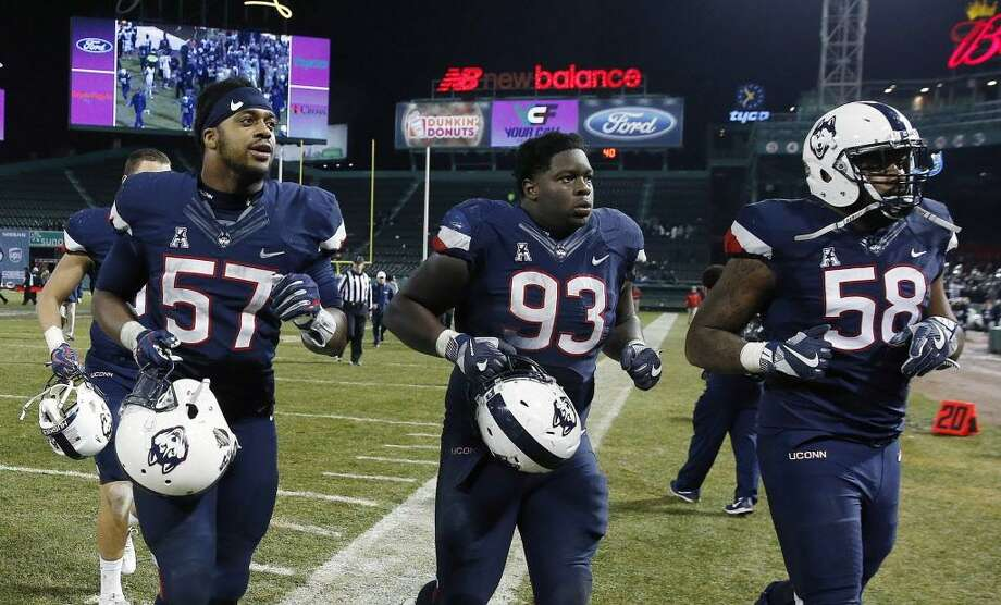 UConn defensive lineman Cole Ormsby (57), defensive lineman Folorunso Fatukasi (93) and defensive lineman Philippe Okounam (58) run off the field following a Nov. 18 game against Boston College. Photo: Michael Dwyer / Associated Press / AP2017