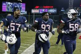 UConn defensive lineman Cole Ormsby (57), defensive lineman Folorunso Fatukasi (93) and defensive lineman Philippe Okounam (58) run off the field following a Nov. 18 game against Boston College.