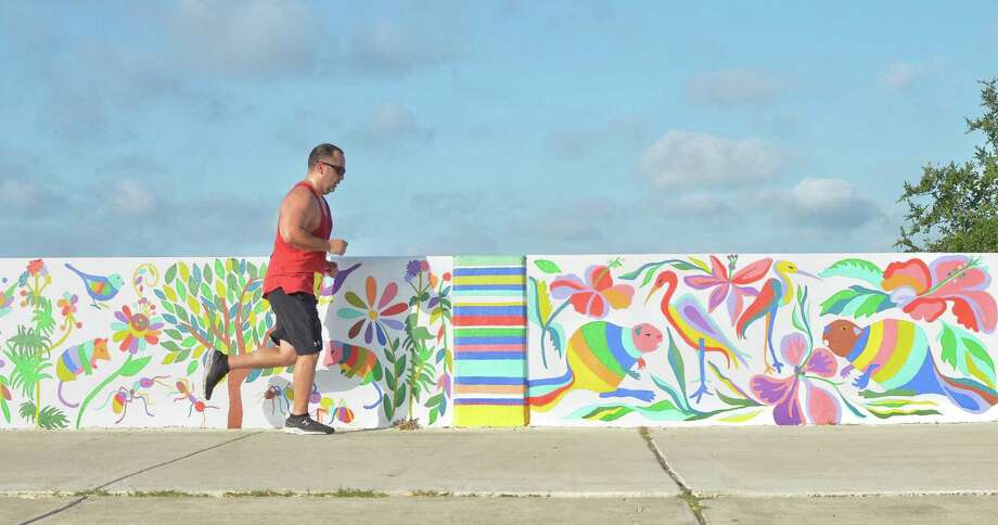 A runner exercises near colorful murals located nearby North Central Park. Photo: Ulysses S. Romero /Laredo Morning Times