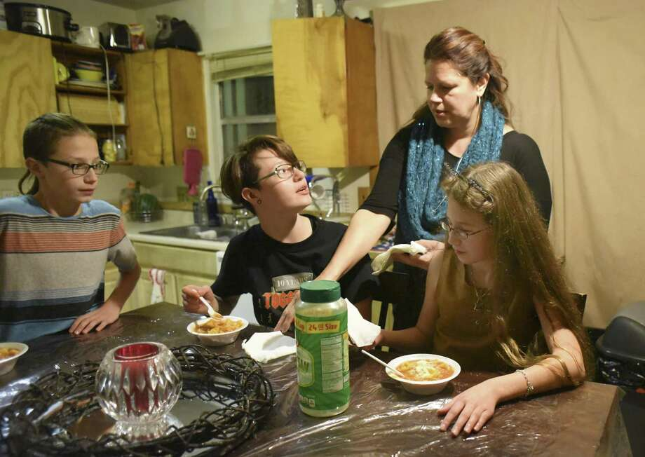 Dakota Flores serves dinner to her children, Tyler Reinn, left, Serenity Grace and Harmonie Lovve. Harmonie Lovve and Tyler Reinn rely on the CHIP program for health insurance. Photo: Billy Calzada, Staff / San Antonio Express-News