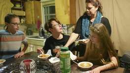 Dakota Flores serves dinner to her children, Tyler Reinn, left, Serenity Grace and Harmonie Lovve. Harmonie Lovve and Tyler Reinn rely on the CHIP program for health insurance.