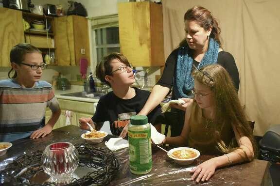 Dakota Flores serves dinner to her children, Tyler Reinn, left, Serenity Grace and Harmonie Lovve. Harmonie Lovve and Tyler Reinn rely on the CHIP program for health insurance.
