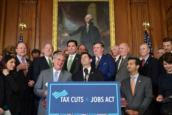 House Majority Leader Kevin McCarthy laughs with House Speaker Paul Ryan (center) during a press conference after the House passed its version of the Republican tax overhaul this month.