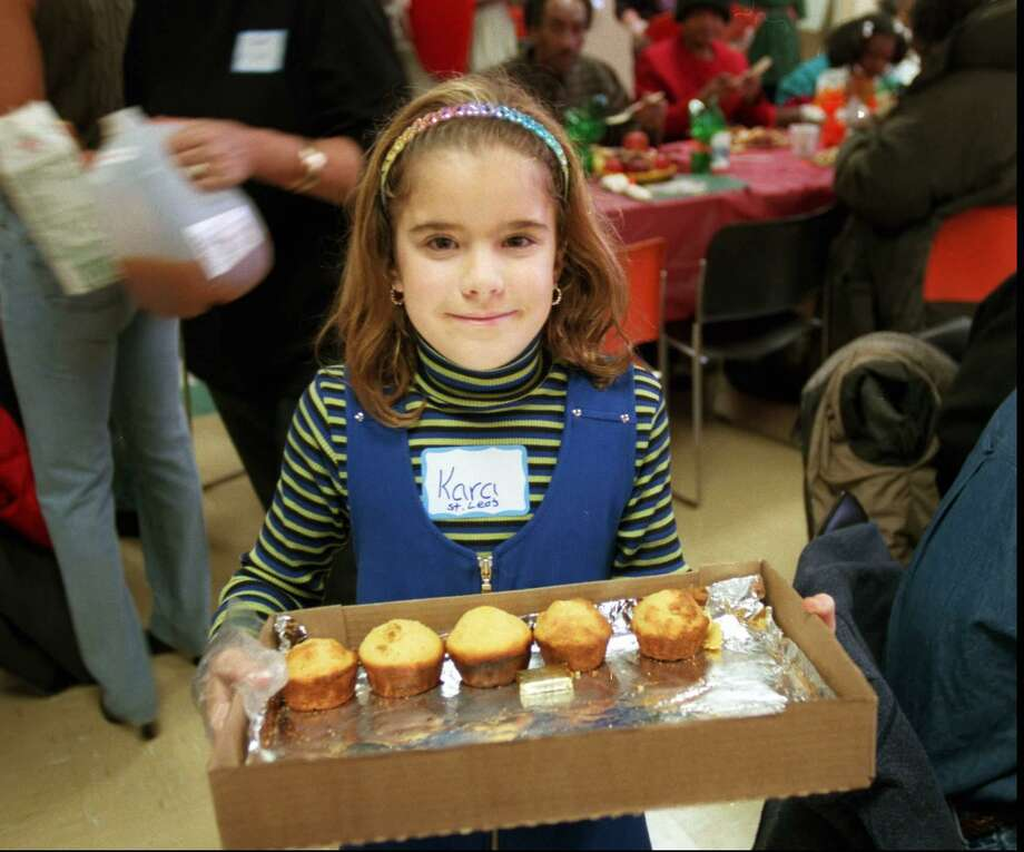 Kara Ferraro, 8, serves corn muffins to the clients at the Thanksgiving Day dinner at the New Covenant House of Hospitality on West Main Street in Stamford on Nov. 27, 1997. She was one of the volunteers from the St. Leo parish. Photo: Tom Ryan / File Photo