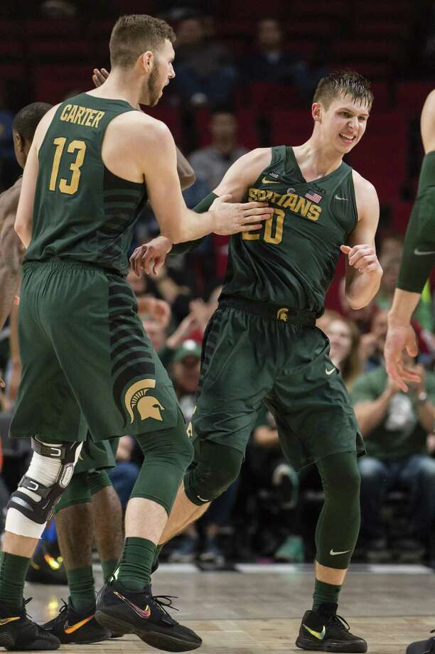 Michigan State guard Matt McQuaid, center, celebrates with forward Ben Carter, left, after making a three point basket during the second half of a game at the Phil Knight Invitational Tournament in Portland, Ore., on Thursday. Photo: Troy Wayrynen / Associated Press / © 2017 Associated Press / All Rights Reserved