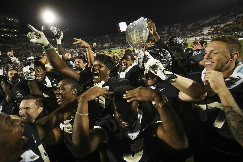 FILE-- The UCF Knights celebrate after a game against the South Florida Bulls at Spectrum Stadium on November 24, 2017 in Orlando, Florida. UCF Knights defeated South Florida Bulls 49-42. Despite an undefeated season, the Knights didn't get an invite to the College Football Playoff this year, finishing 12th in the committee's final ranking. Photo: Logan Bowles, Getty Images