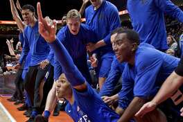 The Duke bench reacts after guard Trevon Duval, bottom, scored after being fouled during the second half of an NCAA college basketball game against Texas in the Phil Knight Invitational tournament in Portland, Ore., Friday, Nov. 24, 2017. (AP Photo/Craig Mitchelldyer)