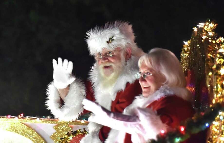 santa and mrs clays wave to the crowd during the 37th annual ford holiday river parade