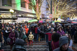 People gather to watch the Christmas tree lighting ceremony at Westlake Center during the fourth annual police brutality and anti-racism protest on Black Friday, Friday, Nov. 24, 2017.