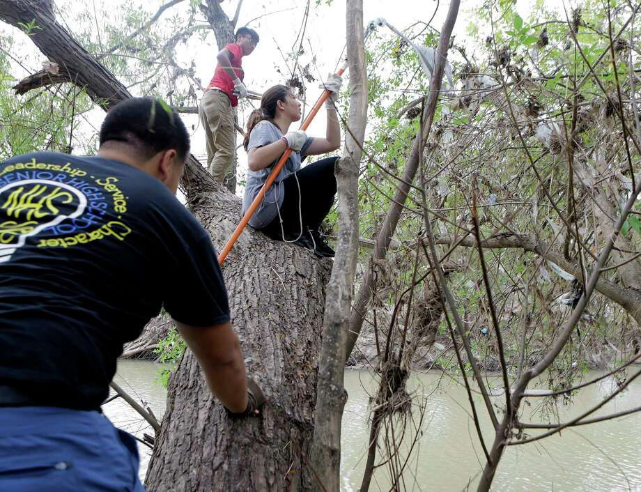 Duyen Nguyen, 18, cleans off debris from a tree  left byHarvey at Buffallo Bayou trails and park on Saturday, Nov. 18, 2017, in Houston. According to officials, over 160 volunteers have been showing up a every weekend since September to help with the clean up efforts. To find a calendar or check on volunteer opportunities at the park, contact them through their website. ( Elizabeth Conley / Houston Chronicle ) Photo: Elizabeth Conley, Chronicle / © 2017 Houston Chronicle