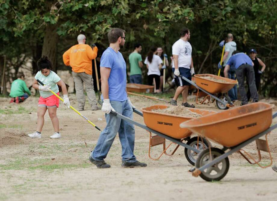 Volunteers shovel silt and debris left from Harvey at Buffallo Bayou trails and park on Saturday, Nov. 18, 2017, in Houston. According to officials, over 160 volunteers have been showing up a every weekend since September to help with the clean up efforts. To find a calendar or check on volunteer opportunities at the park, contact them through their website. ( Elizabeth Conley / Houston Chronicle ) Photo: Elizabeth Conley, Chronicle / © 2017 Houston Chronicle