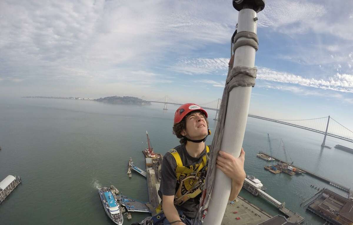 Apprentice steeplejack Kells Phelan inspects the flagpole atop the Ferry Building's clock tower.