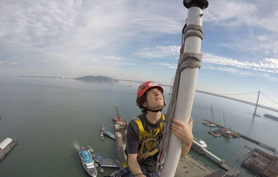 Apprentice steeplejack Kells Phelan inspects the flagpole atop the Ferry Building's clock tower. Photo: Jim Phelan / Jim Phelan
