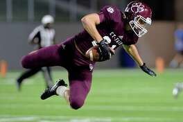 Cody Cunningham (21) of Cy-Fair leaps to avoid a tackle after intercepting a pass in the fourth quarter of a 6A-III area playoff football game between the Cy-Fair Bobcats and the Strake Jesuit Crusaders on November 23, 2017 at Legacy Stadium, Katy, TX.