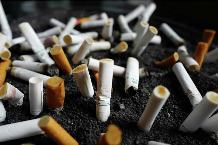 FILE - This Friday, April 7, 2017, file photo, shows cigarette butts discarded in an ashtray outside a New York office building. Decades after they were banned from the airwaves, Big Tobacco companies are returning to prime-time television, but not by choice. Under court order, the tobacco industry for the first time will be forced to advertise the deadly, addictive effects of smoking, more than 11 years after a judge ruled that the companies had misled the public about the dangers of cigarettes. (AP Photo/Mark Lennihan, File)