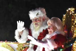 Santa and Mrs Clays wave to the crowd during the 36th Annual Ford Holiday River Parade Friday evening. The parade features 28 illuminated floats decorated for the theme Christmas at the Movies with over 50,000 people expected to attend.