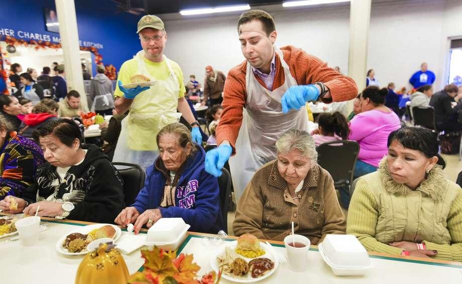 Steven Wright and Jonathan Melendez serve Thanksgiving meals to Laredoans on Thursday at Bethany House of Laredo. Photo: Danny Zaragoza/Laredo Morning Times