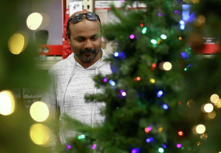Vinesh Viswanathan looks over Christmas trees on Black Friday at the Home Depot in Webster.