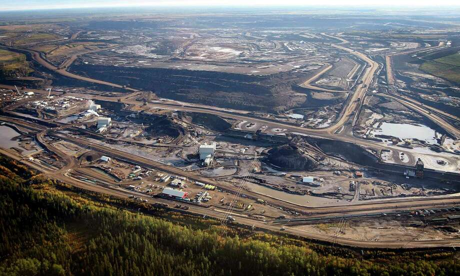 This aerial photo shows a oil sands mine facility near Fort McMurray, in Alberta, Canada. Photo: Jeff McIntosh, SUB / THE CANADIAN PRESS
