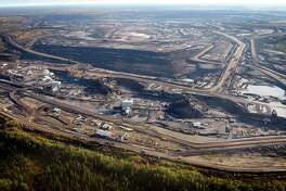 This aerial photo shows a tar sands mine facility near Fort McMurray, in Alberta, Canada. Without pipeline access to Canadian ports, nearly all the country's crude is sold in the United States, much of it heading to Gulf Coast refineries. (AP Photo/The Canadian Press, Jeff McIntosh)