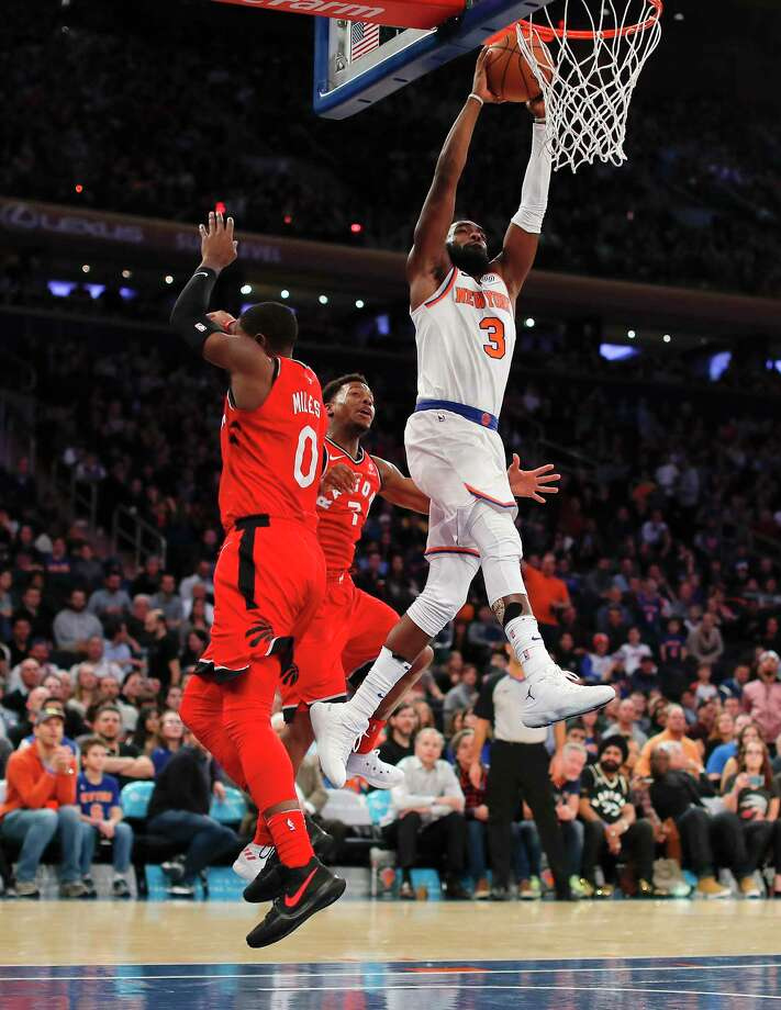 New York Knicks forward Tim Hardaway Jr. (3) goes up to dunk against Toronto Raptors forward CJ Miles (0) and guard Kyle Lowry (7) during the fourth quarter of an NBA basketball game, Wednesday, Nov. 22, 2017, in New York. The Knicks won 108-100. (AP Photo/Julie Jacobson) ORG XMIT: NYJJ119 Photo: Julie Jacobson / Copyright 2017 The Associated Press. All rights reserved.