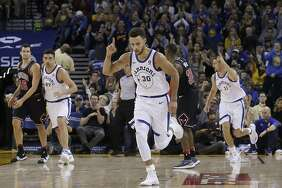 Stephen Curry (30) and Klay Thompson react after Curry scored in the first half Friday night in Oakland.