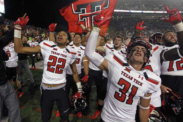 Texas Tech's Da'Leon Ward (22) and Justus Parker (31) celebrate with their teammates after stunning Texas 27-23.
