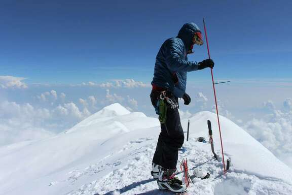 Blaine Horner of CompassData probes the snow pack on top of Denali, the highest point in North America.  Denali National Park in Alaska is among the parks whose entrance fees may more than double.