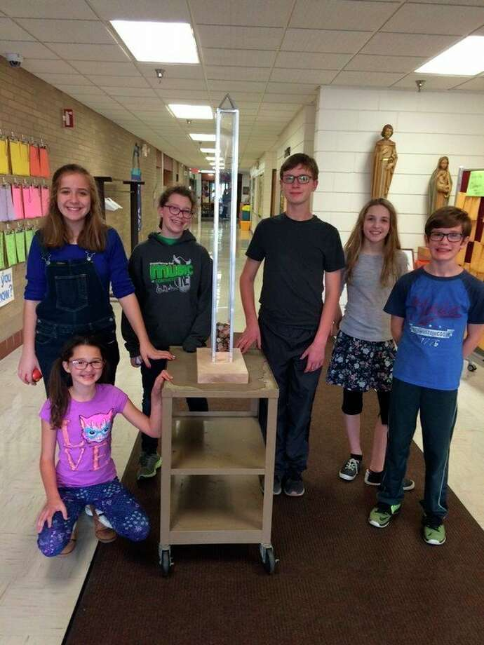 Blessed Sacrament students, from left, Amanda Jendretzke, Sydney Birch, Eleanor Bootman, Eric White, Alana Schroden and Matthew Bootman stand beside the peace pole bank created by Mike Percha, the church's maintenance person.